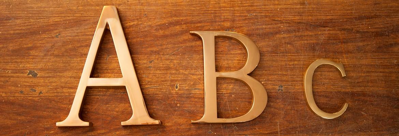 Letras, números y símbolos de latón de distintos tamaños para señalización